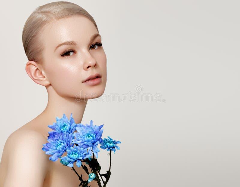 Mujer joven romántica hermosa en una guirnalda de las flores que presentan en un fondo Inspiraci?n de la primavera y del verano P foto de archivo libre de regalías