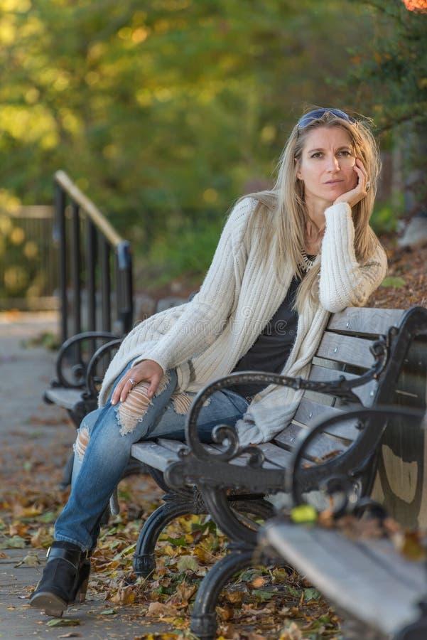 Mujer joven rubia atractiva que se sienta en un banco en parque imagen de archivo