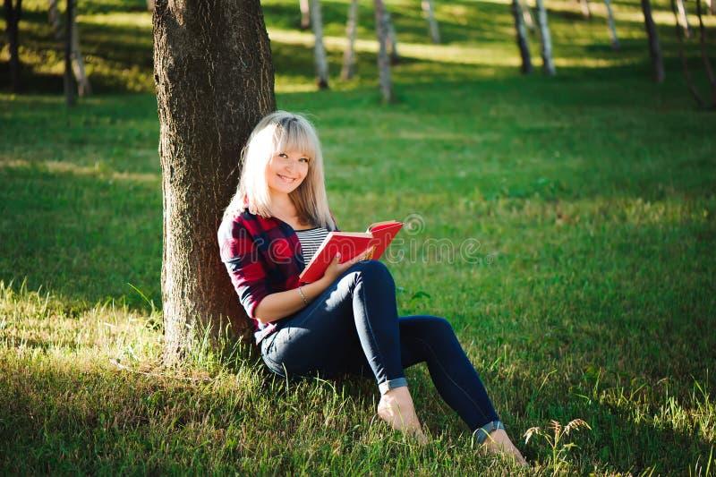 Mujer joven rubia bonita que lee un libro en el parque fotos de archivo libres de regalías