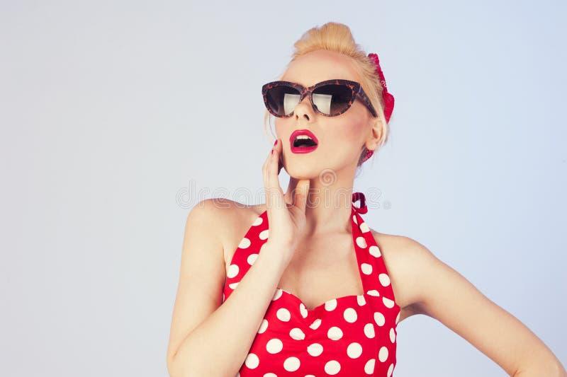 Mujer joven rubia con las gafas de sol que llevan del maquillaje y del peinado del perno-para arriba foto de archivo libre de regalías