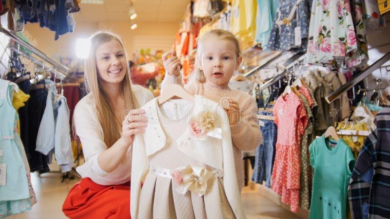 Mujer joven rubia con los niños de compra de la pequeña hija vestido en tienda de la ropa imagen de archivo libre de regalías