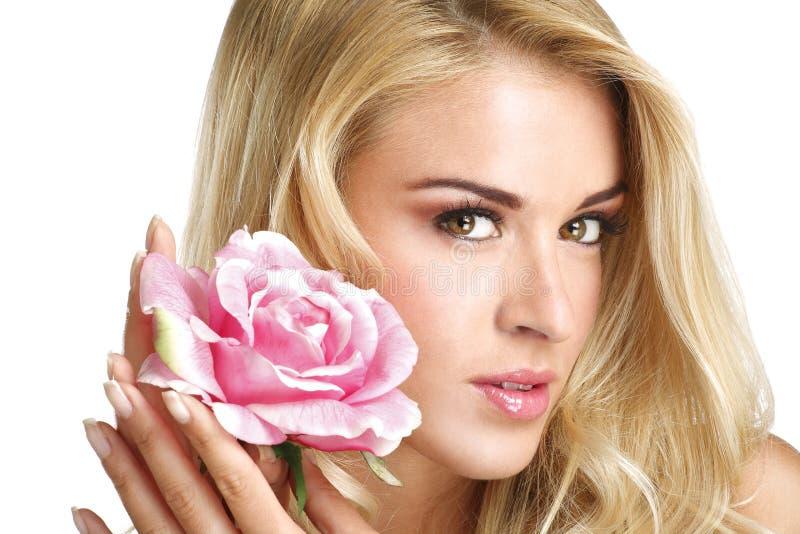 Mujer joven rubia de la belleza que muestra una flor fresca en blanco imágenes de archivo libres de regalías