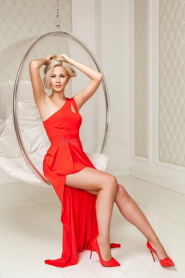 Mujer joven rubia de moda sensual en vestido rojo de igualación brillante con maquillaje y peinado que se sienta y que presenta e fotografía de archivo