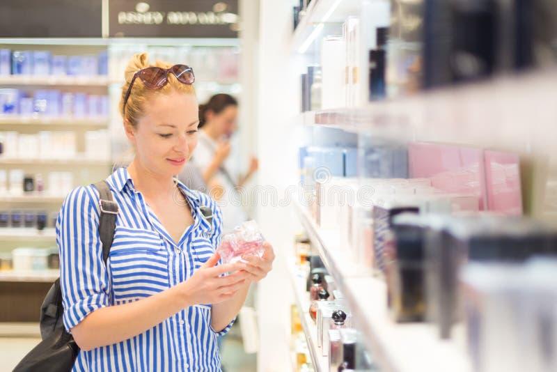 Mujer joven rubia elegante que elige perfume en tienda al por menor imagen de archivo