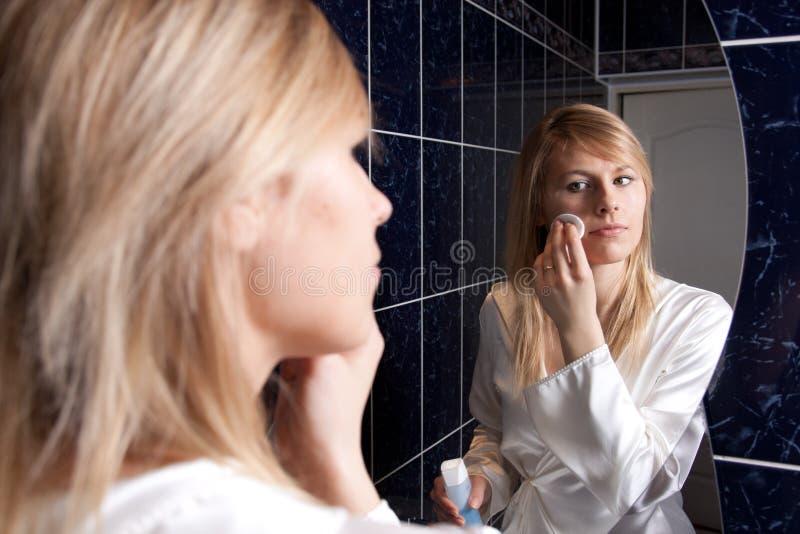 Mujer joven rubia en el cuarto de baño que aplica maquillaje fotos de archivo