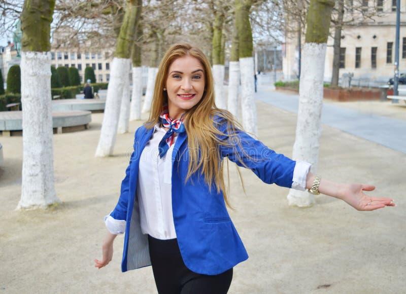 Mujer joven rubia feliz en el parque con la sonrisa enigmática imagenes de archivo