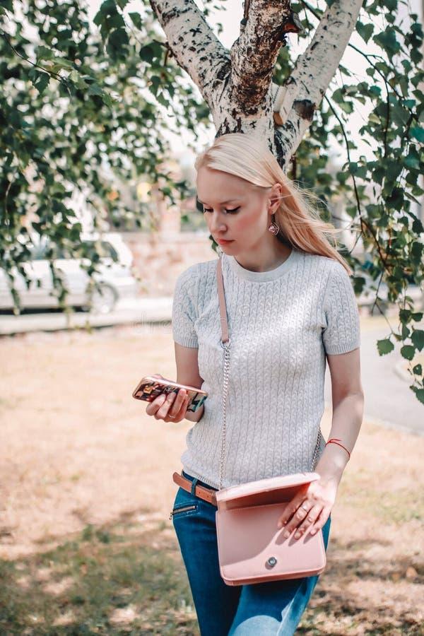 Mujer joven rubia hermosa con el teléfono móvil en la calle imagen de archivo libre de regalías