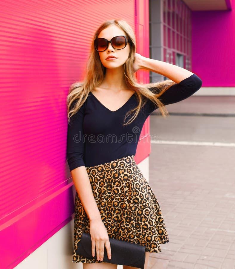 Mujer joven rubia hermosa del retrato en la falda del leopardo, gafas de sol con el embrague del bolso que presenta en la calle d imagen de archivo libre de regalías