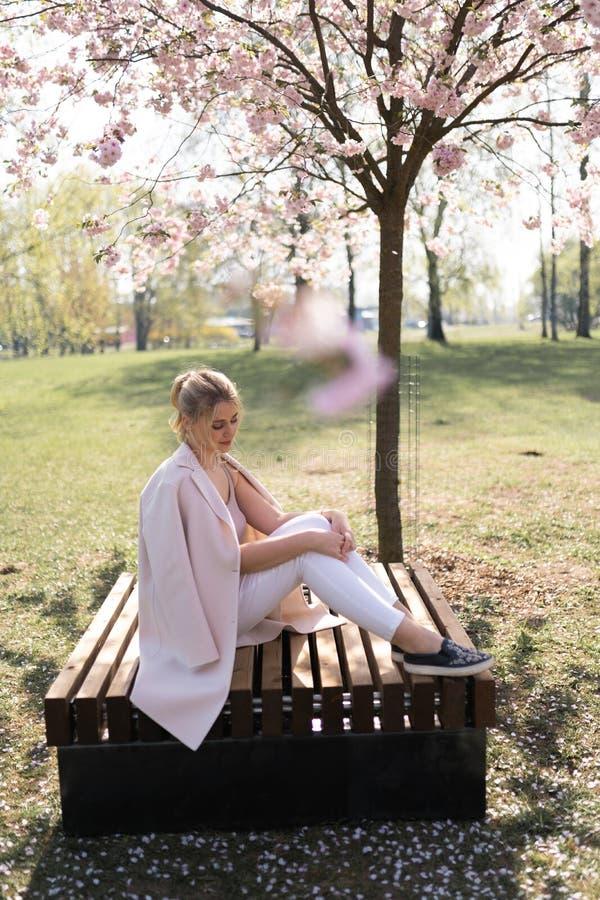 Mujer joven rubia hermosa en el parque de Sakura Cherry Blossom en primavera que disfruta de la naturaleza y del tiempo libre dur fotografía de archivo libre de regalías
