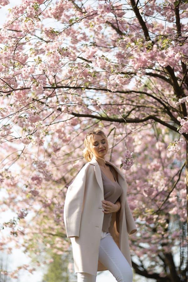 Mujer joven rubia hermosa en el parque de Sakura Cherry Blossom en primavera que disfruta de la naturaleza y del tiempo libre dur imagen de archivo