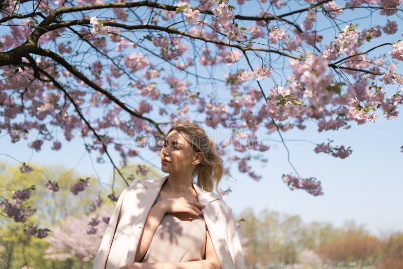 Mujer joven rubia hermosa en el parque de Sakura Cherry Blossom en primavera que disfruta de la naturaleza y del tiempo libre dur imagenes de archivo