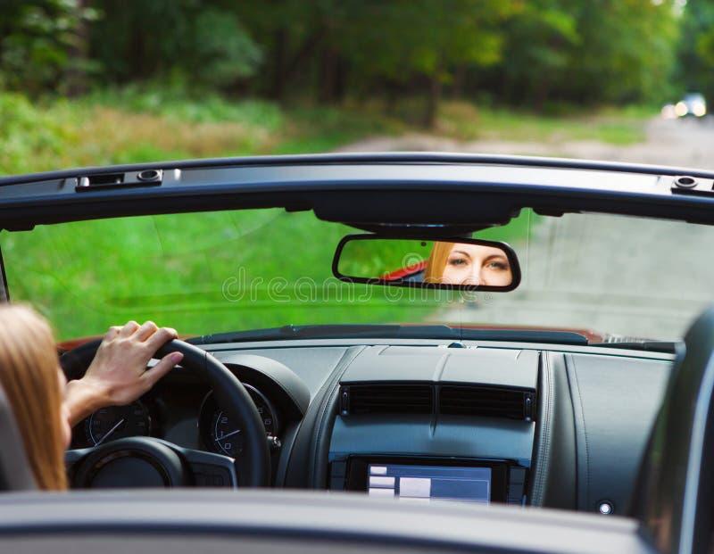 Mujer joven rubia hermosa que conduce un coche de deportes fotografía de archivo libre de regalías