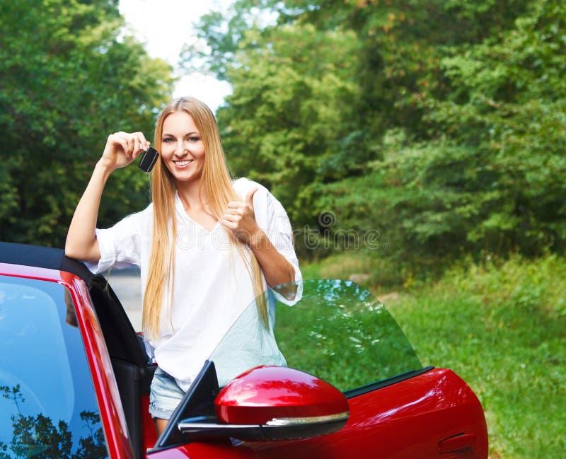 Mujer joven rubia hermosa que se coloca cerca de un coche de deportes imagen de archivo