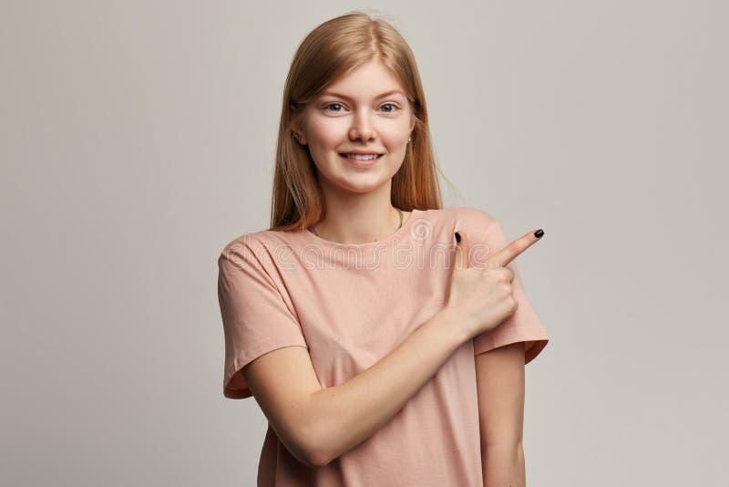 Mujer joven rubia impresionante feliz que señala los fingeres lejos foto de archivo