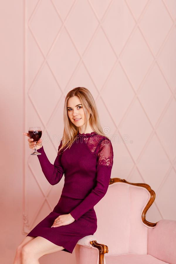 Mujer joven rubia sonriente en un vestido apretado de Borgoña que se sienta en una silla y sostener un vidrio de vino tinto fotos de archivo libres de regalías