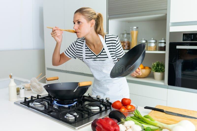 Mujer joven sana que cocina y que prueba la comida con la cuchara de madera en la cocina en casa imagenes de archivo