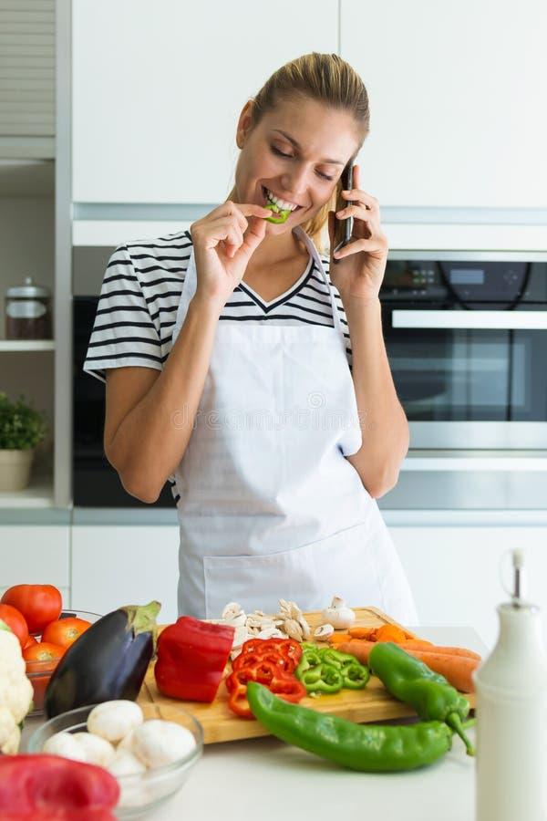Mujer joven sana que come un pedazo de verduras frescas y que habla con su teléfono móvil en la cocina en casa foto de archivo