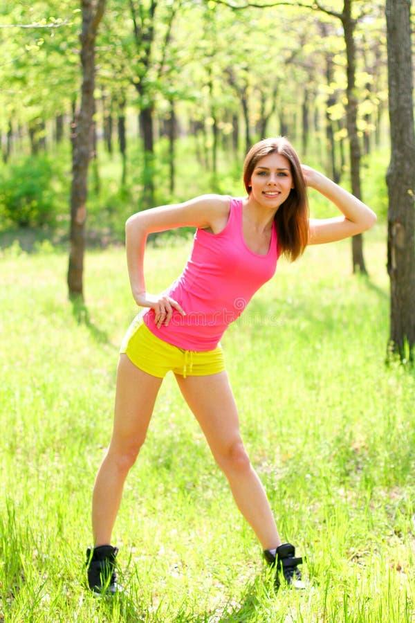 Mujer joven sana que estira antes de aptitud y de ejercicio imagen de archivo libre de regalías