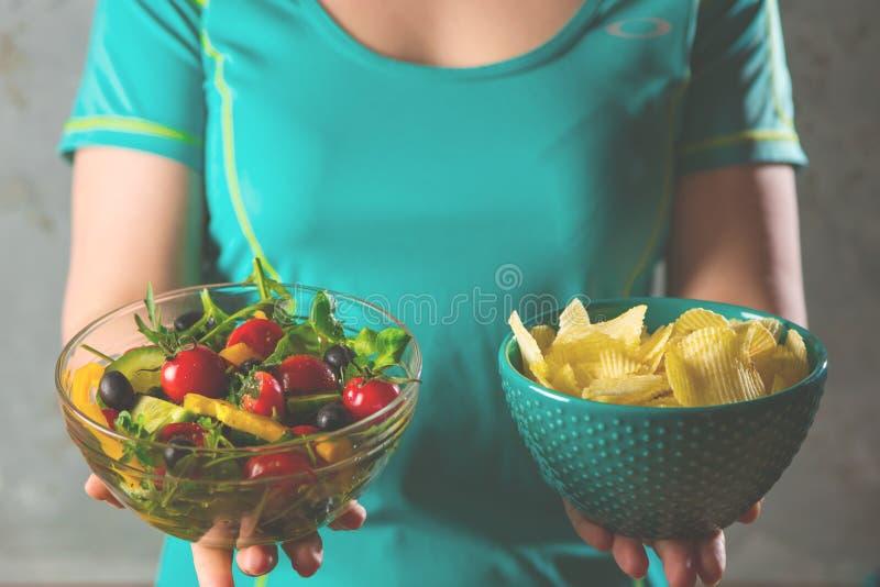 Mujer joven sana que mira comida sana y malsana, intentando tomar la decisión correcta foto de archivo libre de regalías