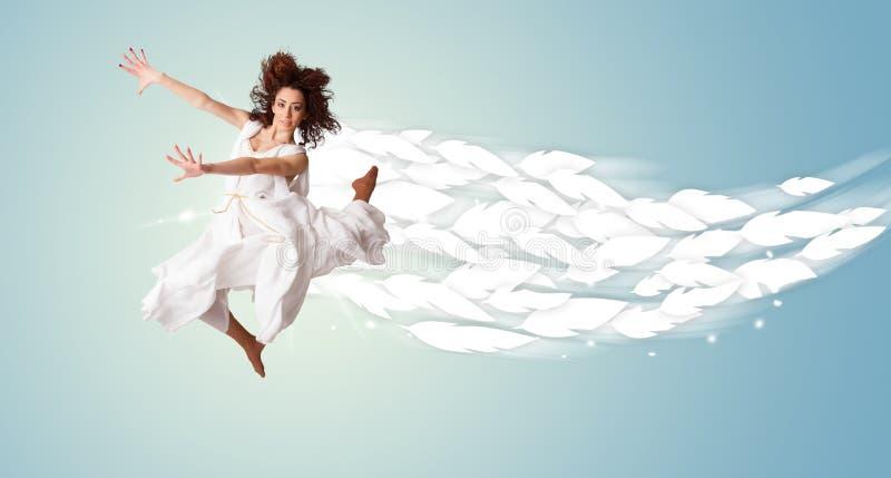 Mujer joven sana que salta con las plumas alrededor de ella fotografía de archivo libre de regalías