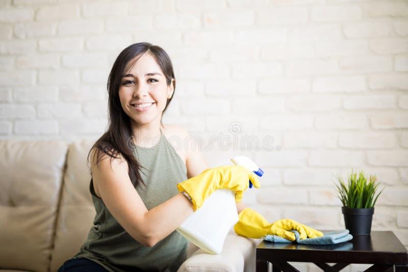 Mujer joven satisfecha que usa un trapo y un espray mientras que limpia furni foto de archivo libre de regalías