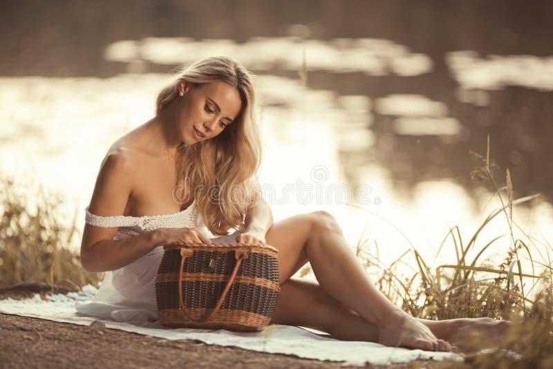 Mujer joven sensual en la comida campestre que se sienta por el lago en la puesta del sol y que mira en cesta de la comida campes fotografía de archivo