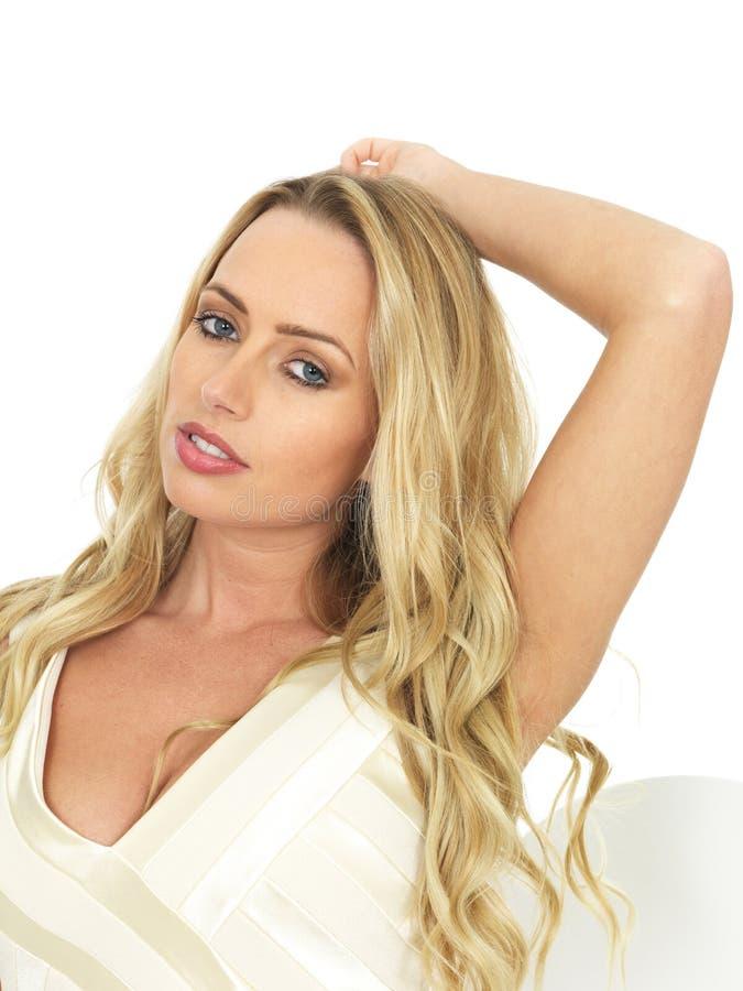 Mujer joven sensual hermosa que juega con su pelo rubio largo que parece relajado fotografía de archivo