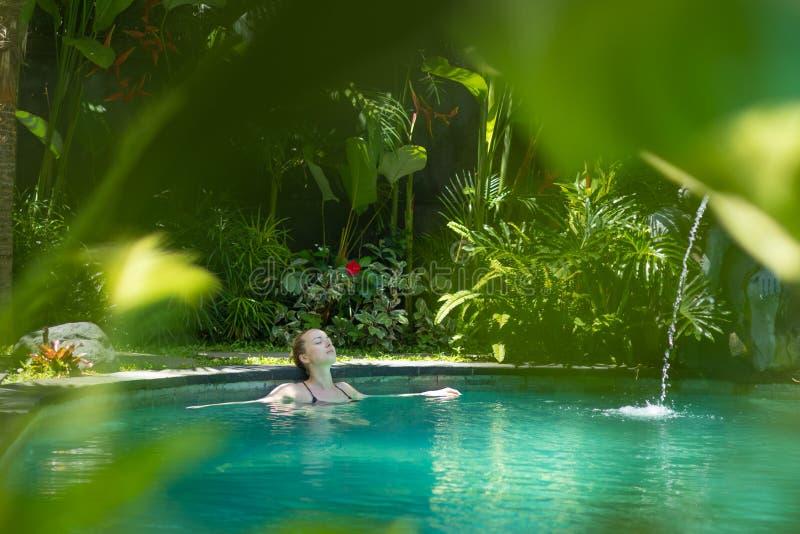 Mujer joven sensual que se relaja en la piscina al aire libre del infinito del balneario rodeada con el verdor tropical enorme de fotos de archivo