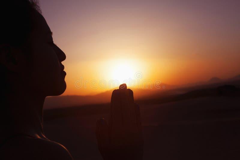 Mujer joven serena con las manos junto en actitud del rezo en el desierto en China, silueta, ajuste del sol fotografía de archivo