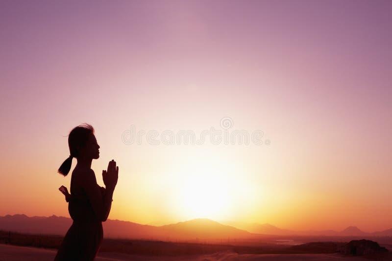 Mujer joven serena con las manos junto en actitud del rezo en el desierto en China, silueta, perfil, ajuste del sol imagenes de archivo