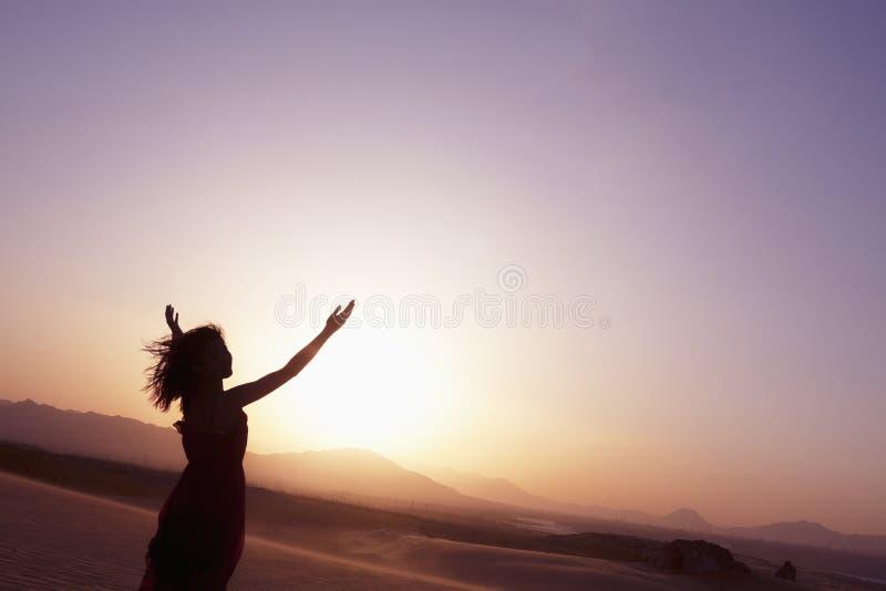 Mujer joven serena con yoga que hace extendida de los brazos en el desierto en China, silueta imagenes de archivo