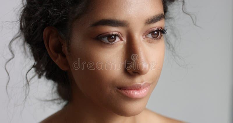 Mujer joven serena feliz con los ojos ideales verdes olivas hermosos de la piel y de la piel y del marrón del pelo rizado en estu imagen de archivo libre de regalías