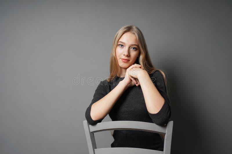 Mujer joven serena que se sienta a horcajadas en silla fotografía de archivo
