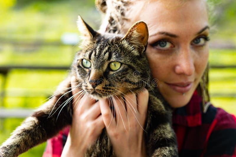 Mujer joven seria atractiva que sostiene su gato del animal doméstico foto de archivo