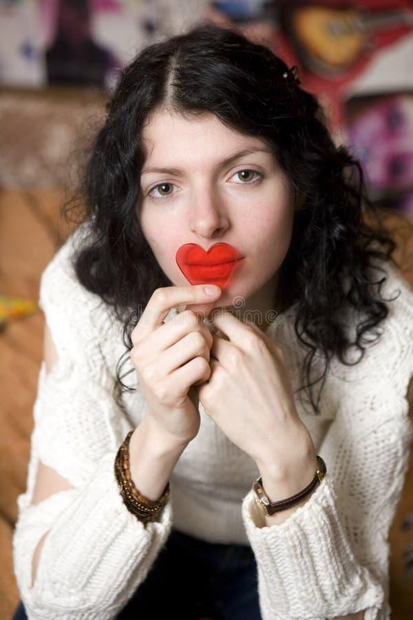 Mujer joven seria con los labios próximos del corazón plástico foto de archivo libre de regalías