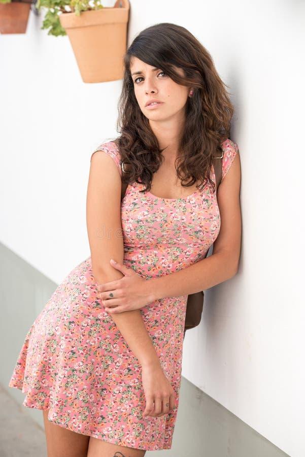 Mujer joven seria con un vestido rosado que plantea la reclinación sobre una pared blanca en Badajoz, Extremadura, España imágenes de archivo libres de regalías