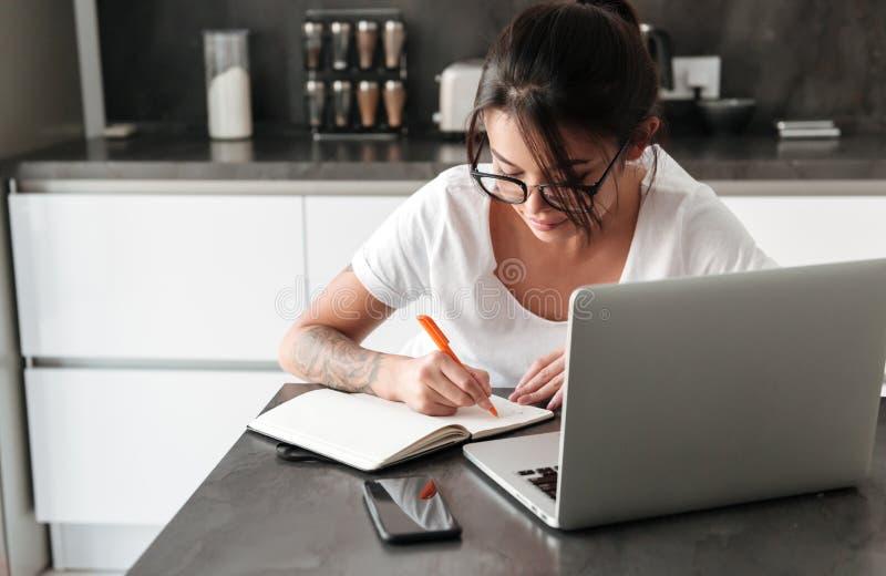 Mujer joven seria concentrada que usa notas de la escritura del ordenador portátil imagen de archivo libre de regalías