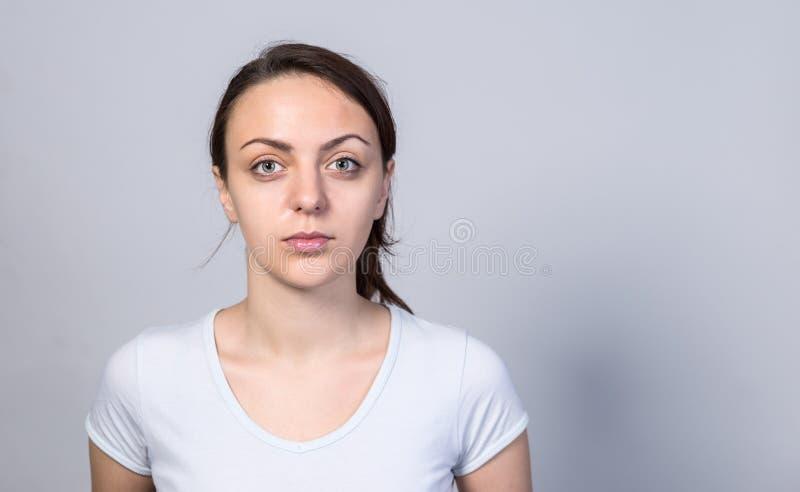 Mujer joven seria contra el fondo blanco imagenes de archivo