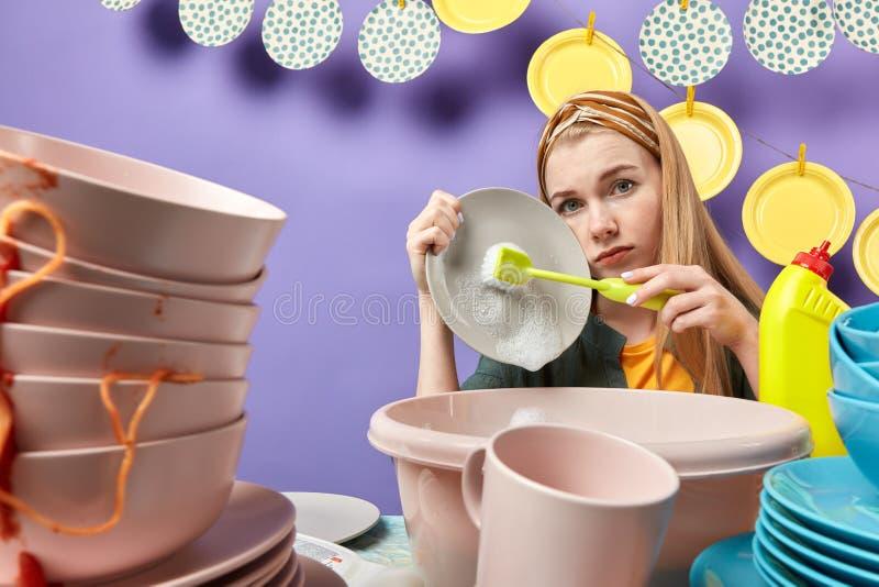 Mujer joven seria infeliz triste usando cepillo mientras que hace tareas de hogar fotografía de archivo