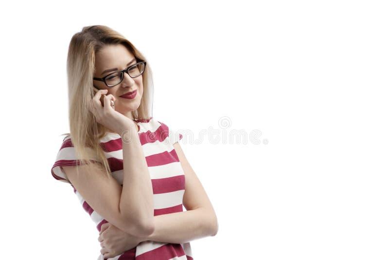Mujer joven seria que habla en el teléfono aislado en blanco Copie el espacio y fórmelo Mujer europea hermosa y feliz que habla e fotografía de archivo