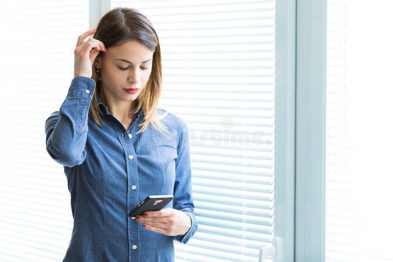 Mujer joven seria que lee un mensaje de texto imagenes de archivo