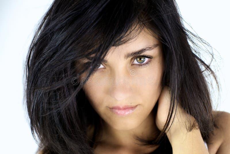 Mujer joven seria que mira con los ojos verdes fotografía de archivo libre de regalías
