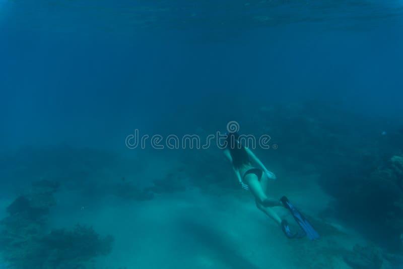 Mujer joven snorkling bajo el filón y coral del mar del agua Vocación del verano imagen de archivo libre de regalías
