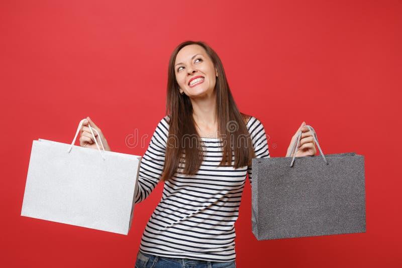 Mujer joven soñadora en la ropa rayada que mira para arriba, sosteniendo bolsos de los paquetes con las compras después de hacer  foto de archivo libre de regalías