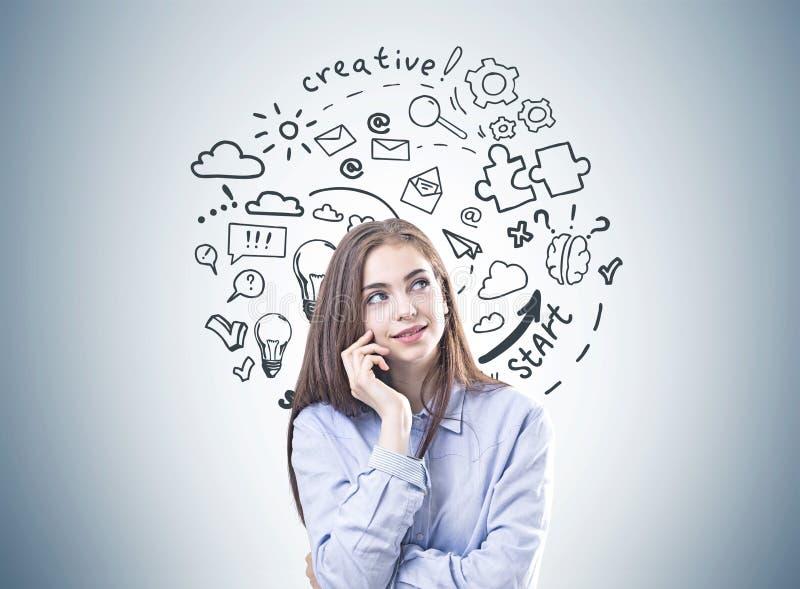 Mujer joven soñadora en una camisa azul, pensamiento creativo fotografía de archivo libre de regalías