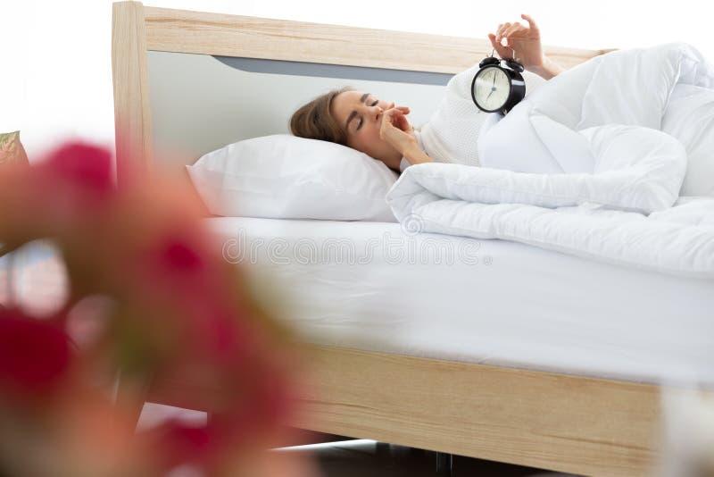 Mujer joven soñolienta que intenta el despertador cercano imagen de archivo