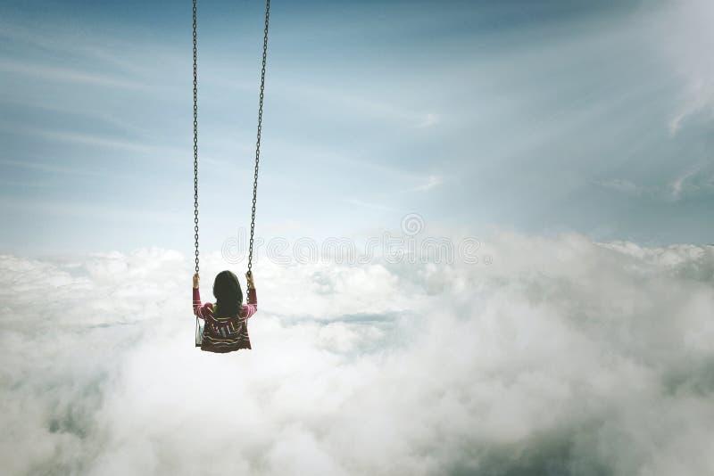 Mujer joven sola con el oscilación sobre la nube foto de archivo