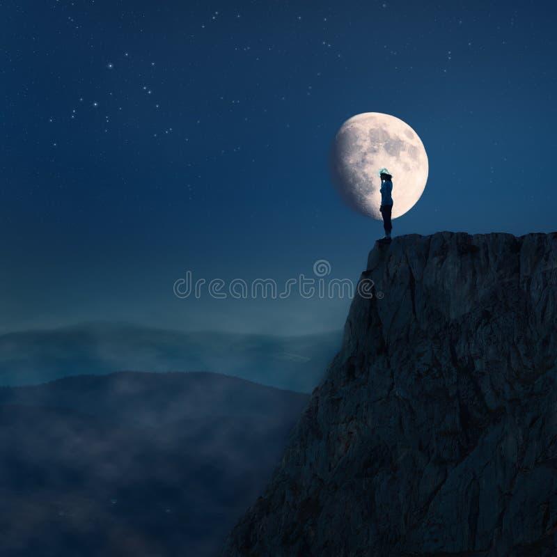 Mujer joven sola encima de un acantilado en la noche foto de archivo