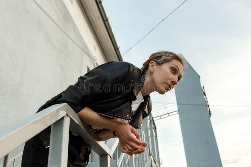 Mujer joven sola melanc?lica en la chaqueta de cuero negra que presenta en las escaleras con la pared en fondo Concepto de soleda imagen de archivo