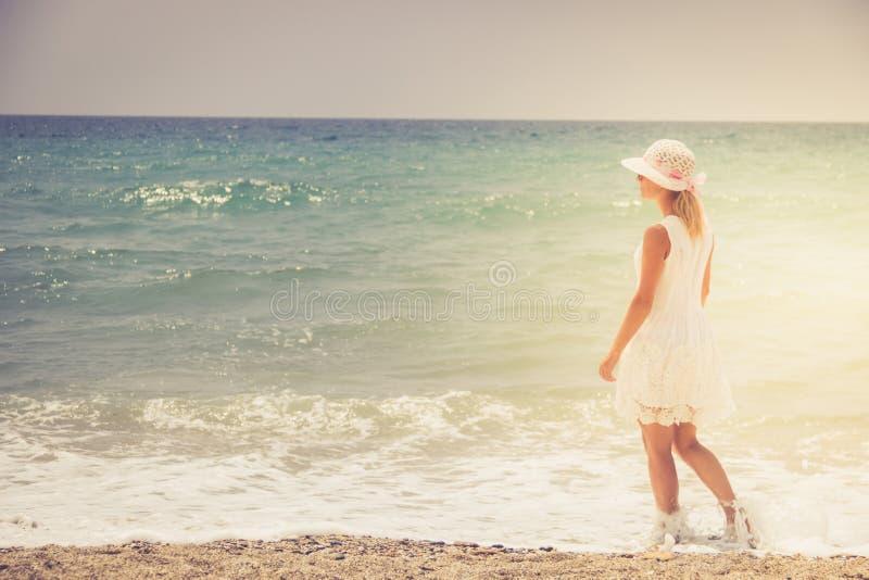 Mujer joven sola que camina en la playa de la puesta del sol fotografía de archivo libre de regalías